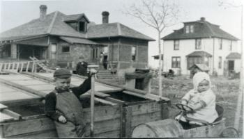 Red Deer Archives, P1754; Three children behind some houses, 19-?