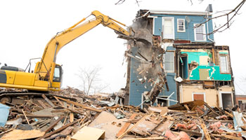 bulldozer demolishing a house with rubble lying everywhere
