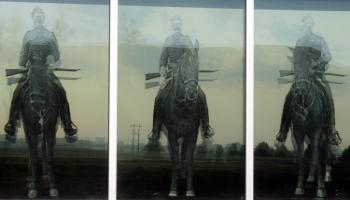 Three glass windows with an RCMP officer on horseback etched in the glass on each one.