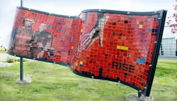 Red side of a rectangle sculpture made up of glass tiles an the photo etched tiles that show police and emergency services personnel and and out-reading hands trying to join. The word
