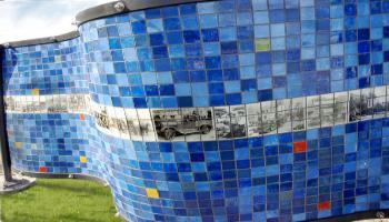 Blue side of a rectangle sculpture made up of glass tiles an the photo etched tiles of old photographs.