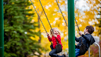 Photo of Little boy and girl on swing
